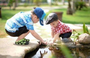 Two young boys playing in the pond