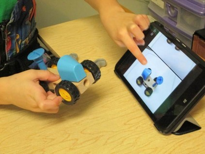 Student building a truck using a picture on a tablet for guidance