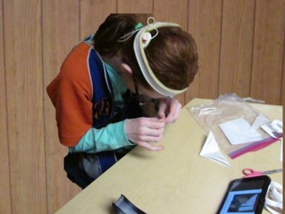 Student with poor upper body strength bent over a desk looking closely at hands while trying to complete an activity