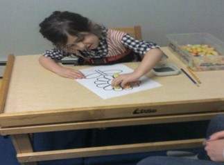 Student with poor upper body strength leaning to the right while trying to complete a craft activity