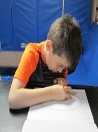 Student tracing a paper plate