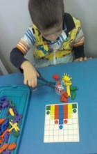 """Student completing a puzzle using a """"grabber"""" to manipulate the materials"""
