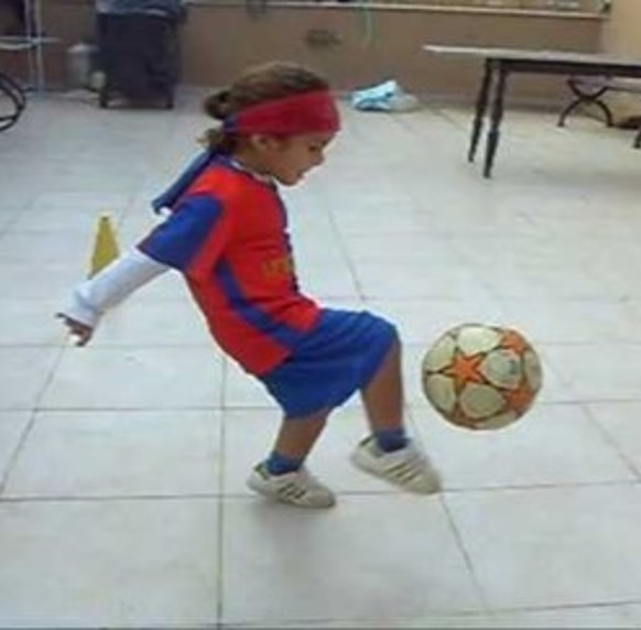 This photo shows a youngster kicking a soccer ball.  The child's arms are held backward while the head is tipped forward.