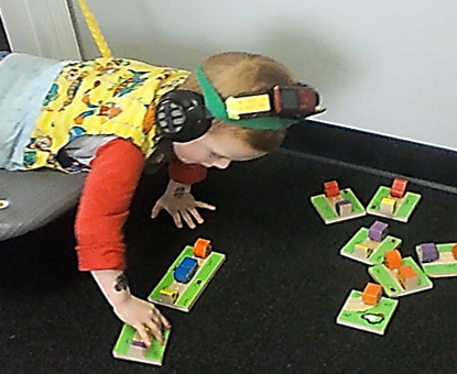 this photo shows a child who is prone on a platform swing.  He is playing a game with wooden car & truck dominoes.  The vehicles are posed in different spatial orientations.