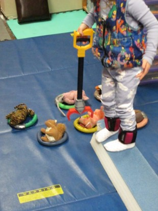this photo shows a child who is standing erect on a balance beam while using a reacher to place small stuffed animals into rings.