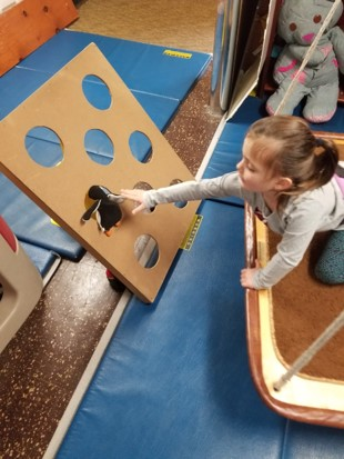 his photo shows a girl who is kneeling on a platform swing, reaching toward a target board of holes to push a stuffed animal through one of the holes.