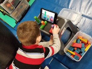 this photo shows a boy who is reaching to build a tower of blocks.  He is sitting on a tire swing and his back and head are extended as he reaches to assemble the blocks as shown on a tablet.