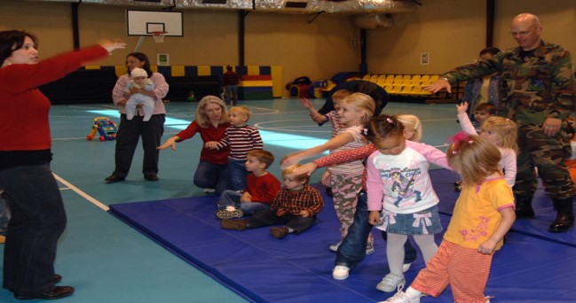 photo of children playing Hokey Pokey in a military gym