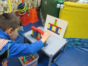 This photo shows a boy building a block design from a task card