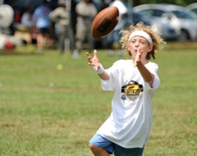 This photo shows a girl catching a football