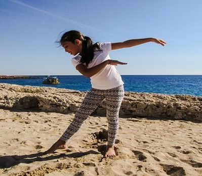 This photo shows a girl on a beach performing a dance move with her arms and legs